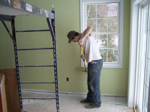 Pintor realizando trabalho com tinta em parede residencial