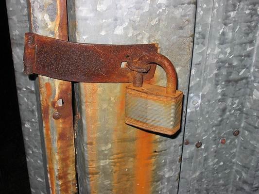 Porta em chapa de aço com proteção e cadeado enfferjudado pela ação do tempo
